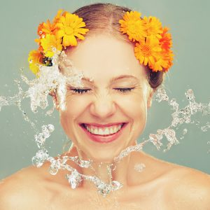 beauty laughing girl with splashes of water and yellow flowers